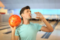 Man holds ball and drinks water in bowling club Stock Photo