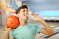 Man holds ball and drinks water in bowling club Stock Image