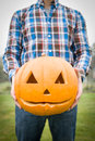 Man holds halloween pumpkin standing outside in plaid shirt and blue jeans is holding in front of him a Royalty Free Stock Photography