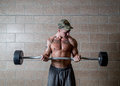 Man holds weights at level ofd umbilicus athlete in shorts with tattoo on his chest in the gym holding a bar with the of the as a Royalty Free Stock Image