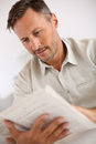 Man at home relaxing and reading newspaper relaxed handsome Stock Photography