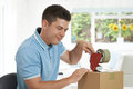 Man At Home Sealing Box For Dispatch Royalty Free Stock Photo