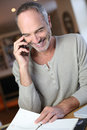Man at home talking on phone mature working from Stock Images