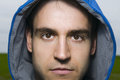 Man with hood serious portrait of a young in the front head directly to the camera looking at the blue hooded Royalty Free Stock Photo