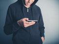 Man in hooded top using his smartphone a young wearing a is Royalty Free Stock Images