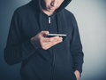Man in hooded top using his smartphone a young wearing a is Stock Photography