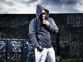 Man in hoodie in front of graffiti portrait a black wall and stormy looking sky Stock Photography
