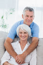 Man hugging his wife who is sitting on the couch mature men Stock Photo