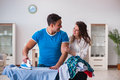The man husband ironing at home helping his wife Royalty Free Stock Photo