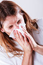 Man with hygienic tissue allergy and cold concept young long haired sick guy blowing nose Stock Image