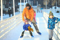 Man ice skating with son