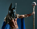 The man in the image of ancient egyptian pharaoh with a mask anubis on his face on blue background Stock Photography