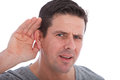 Man with impaired hearing struggling to hear frowning as he holds his hand his ear in an attempt improve acoustics Stock Images