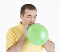 Man inflates the balloon a green ball on a light background Stock Images