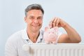 Man inserting coin in piggy bank portrait of a kept on radiator Royalty Free Stock Photos