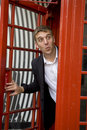Man inside traditional English red telephone box Royalty Free Stock Image