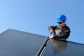 Man installing alternative energy photovoltaic pan solar panels on roof Royalty Free Stock Photo