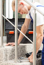 Man installing a bannister young working tightening bolts whith wrench Royalty Free Stock Photo