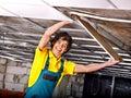Man installing suspended ceiling in builder uniform Stock Image