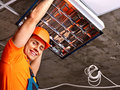 Man installing suspended ceiling in builder uniform Stock Photo