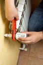 Man installing valve on heating radiator Royalty Free Stock Photo