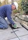 Man installs flagstone on patio Royalty Free Stock Photo