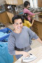 Man Ironing Clothes With Family In Kitchen Royalty Free Stock Image