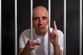 Man in jail gesturing guns with his hands Royalty Free Stock Photo