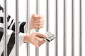 Man in jail holding prison bars and giving bribe isolated on white background Stock Photography