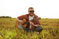 Man in jeans sits and plays guitar on grass Stock Image
