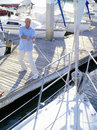 Man on jetty pulling rope attached to boat elevated view Stock Image