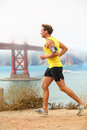 Man jogging male running in san francisco sporty fit young jogger along a dirt track alongside bay and golden Royalty Free Stock Photography
