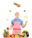 Man juggling with fruits behind a table full of fruits and veget vegetables isolated on white background Royalty Free Stock Photos
