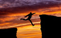 Man jumping across the gap from one rock to cling to other over rocks with on sunset fiery background element Royalty Free Stock Photo