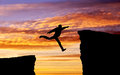Man jumping across the gap from one rock to cling to other over rocks with on sunset fiery background element Stock Photos