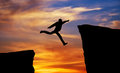 Man jumping across the gap from one rock to cling to other over rocks with on sunset fiery background element Royalty Free Stock Image