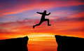 Man jumping across the gap from one rock to cling to the other. Royalty Free Stock Photo