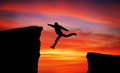 Man jumping across the gap from one rock to cling to the other over rocks with on sunset fiery background element Royalty Free Stock Image