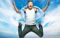 Man jumping against sky funny in blue shirt and jeans blue Stock Photo