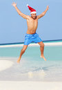 Man jumping on beach wearing santa hat having fun Stock Photography