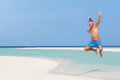 Man jumping on beach wearing santa hat smiling Royalty Free Stock Photos