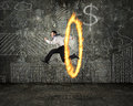 Man jumping through fire hoop with doodles wall Royalty Free Stock Photo