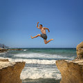 Man jumping over the abyss between two rocky mountains. Royalty Free Stock Photo
