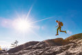 Man jumping over gap on mountain hike Royalty Free Stock Photo