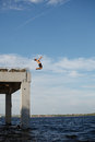 Man jumping into sea from pier