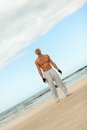 Man is jumping sport karate martial arts fight kick jump beach summertime Royalty Free Stock Image