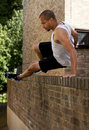 Man jumping a wall Stock Photography
