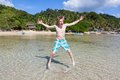 Man jumping in water young on a sunny beach philippines Stock Image
