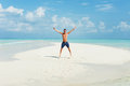 Man jumps on the beautiful beach background of with white sand and cloudy sky Royalty Free Stock Images