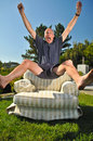 Man jumps into a chair Stock Image